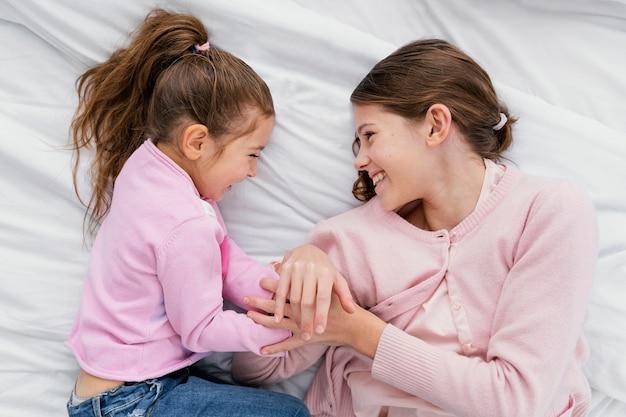 Bovenaanzicht van twee kleine smileyzusjes die thuis samen spelen