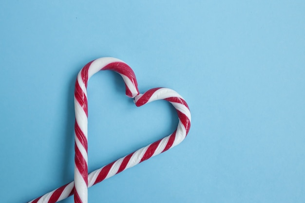 Bovenaanzicht van twee kleurrijke snoep stokken gerangschikt in hart op blauwe achtergrond