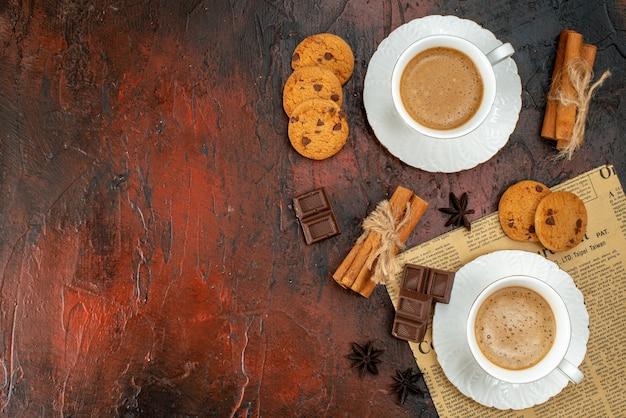 Bovenaanzicht van twee kopjes koffiekoekjes, kaneellimoenen, chocoladerepen op een oude krant aan de linkerkant op een donkere achtergrond