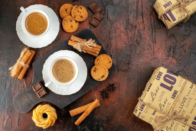 Bovenaanzicht van twee kopjes koffiekoekjes, kaneellimoenen, chocoladerepen op houten snijplank en geschenkdozen op donkere achtergrond