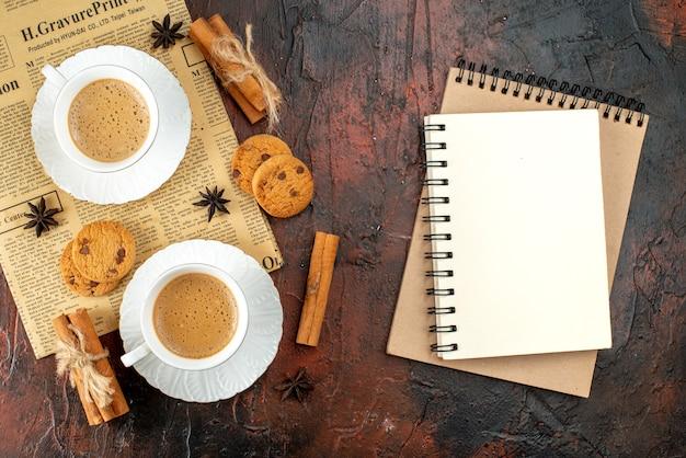 Bovenaanzicht van twee kopjes koffiekoekjes, kaneellimoenen op een oude krant en notitieboekjes op een donkere achtergrond