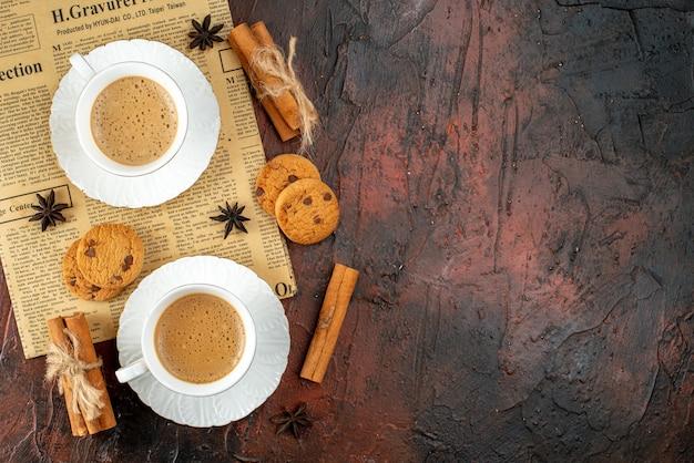 Bovenaanzicht van twee kopjes koffiekoekjes kaneellimoenen op een oude krant op donkere achtergrond