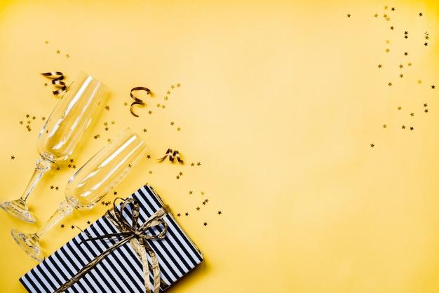Bovenaanzicht van twee kristallen champagneglazen, een geschenkdoos en stervormige gouden confetti over geel