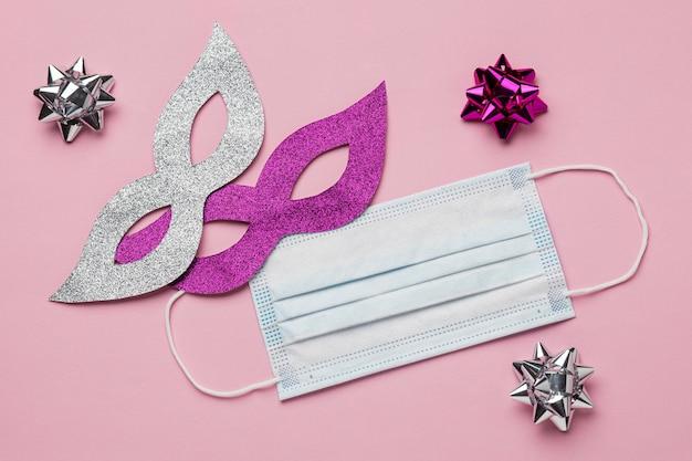 Bovenaanzicht van twee maskers voor carnaval met medisch masker en bogen