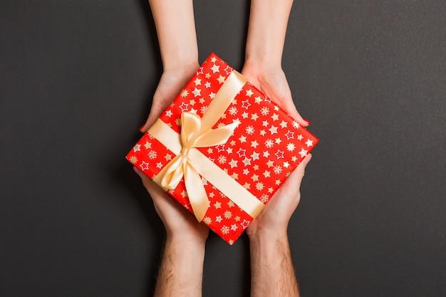 Bovenaanzicht van twee mensen die een cadeau of geschenk delen. vakantie en verrassingsconcept.