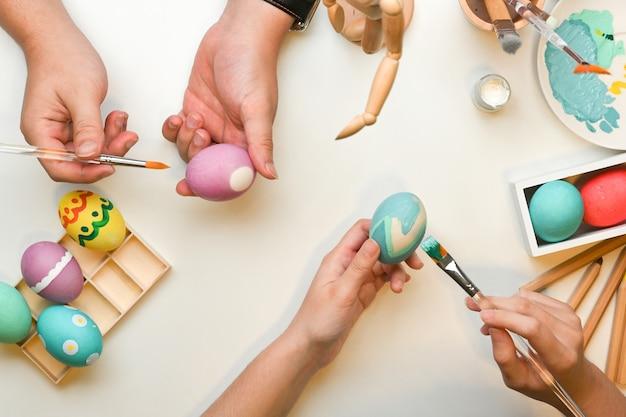 Bovenaanzicht van twee mensen handen schilderen op eieren, voorbereiding voor pasen festival thuis