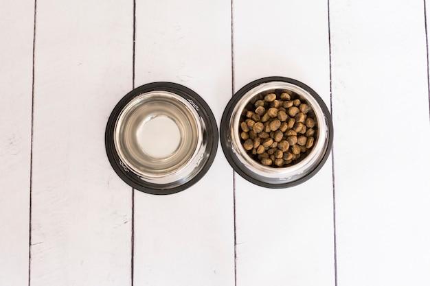 Bovenaanzicht van twee metalen kommen, één met hondenvoer en de andere met water