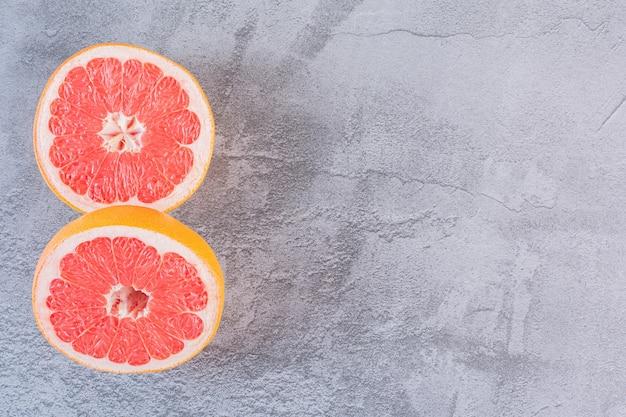 Bovenaanzicht van twee plakjes verse grapefruit op grijs.