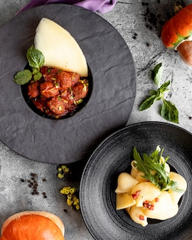 Bovenaanzicht van twee platen met gehaktballetjes in tomatensaus en schelpen pasta