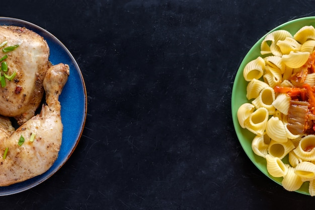Bovenaanzicht van twee platen met pasta en gebakken kip copyspace