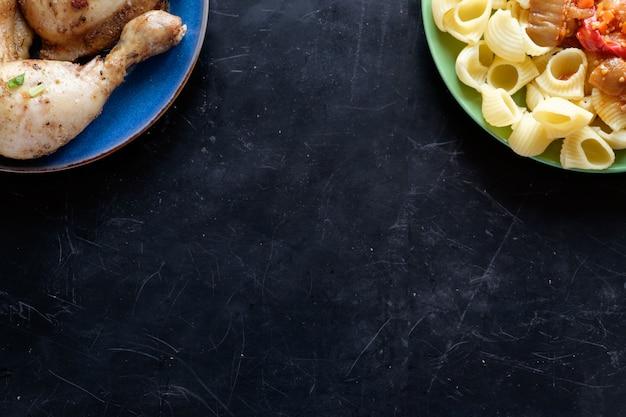 Bovenaanzicht van twee platen met pasta en gebakken kip kopie ruimte