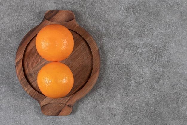Bovenaanzicht van twee rijpe sinaasappelen op houten dienblad over grijze tafel.