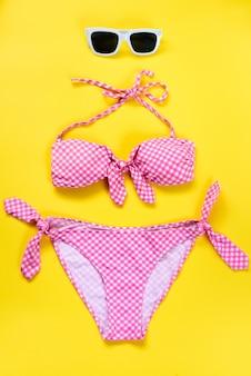 Bovenaanzicht van twee stukken roze geruit zwempak en witte zonnebril op geel