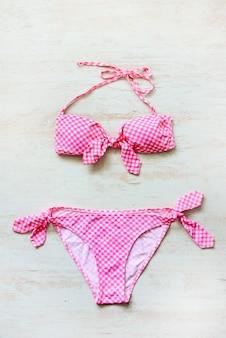 Bovenaanzicht van twee stukken roze geruit zwempak op houten