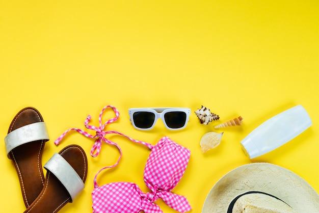 Bovenaanzicht van twee stukken roze zwemkleding en strand accessoties op gele achtergrond.