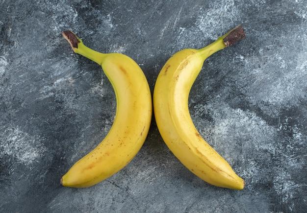 Bovenaanzicht van twee verse rijpe bananen over grijze achtergrond.