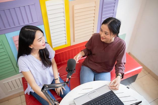 Bovenaanzicht van twee vrouwen die praten met microfoons tijdens podcast