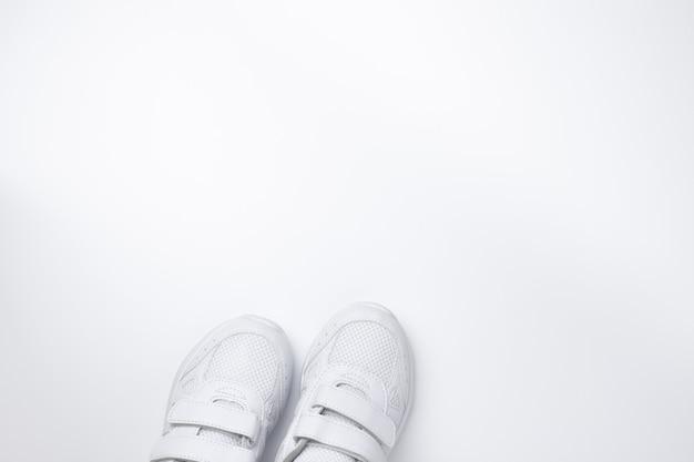 Bovenaanzicht van twee witte hardloopschoenen gedeeltelijk aan de onderkant met vrije ruimte voor tekstisolatie...