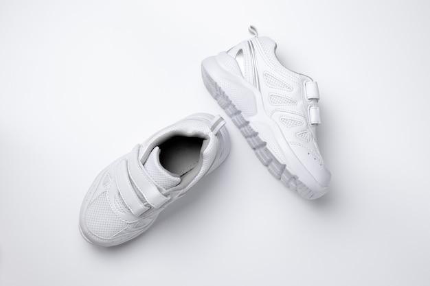 Bovenaanzicht van twee witte kindersneakers met klittenband voor gemakkelijk schoeisel geïsoleerd op een witte ...