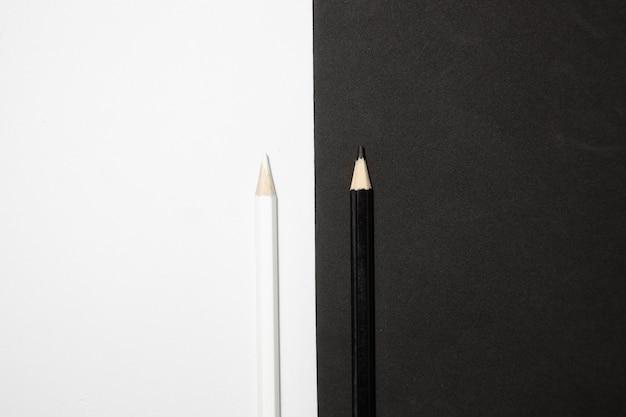 Bovenaanzicht van twee zwart-witte houten potloden op een zwart-witte achtergrond