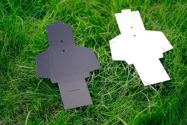 Bovenaanzicht van twee zwarte en witte lege ongevouwen dozen voor accessoires voor het naaien van kledinglabels op groen...