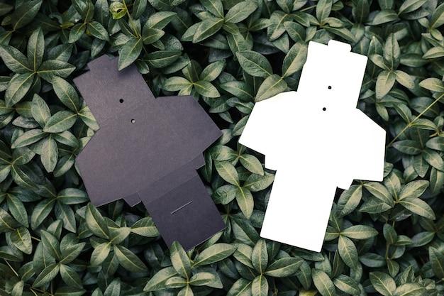 Bovenaanzicht van twee zwarte en witte lege ongevouwen dozen voor accessoires voor het naaien van tags voor kleding op ba...