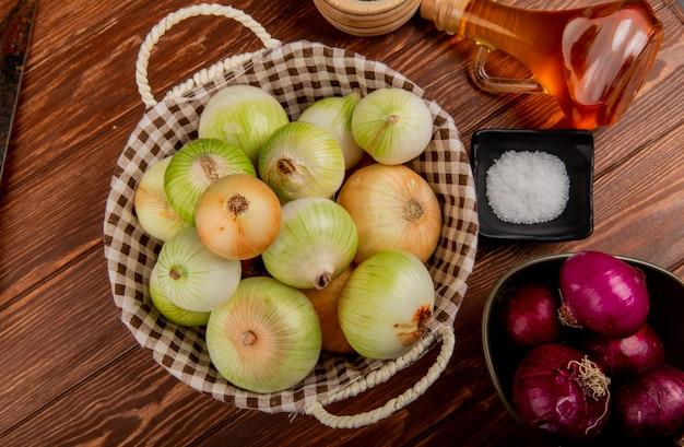 Bovenaanzicht van uien als rode en witte in kom en mand met boterzout op houten achtergrond