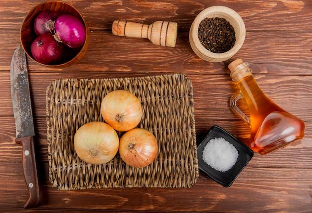 Bovenaanzicht van uien als rode en zoete in kom en in mand plaat met boter zout zwarte peper zaden en mes rond op houten achtergrond