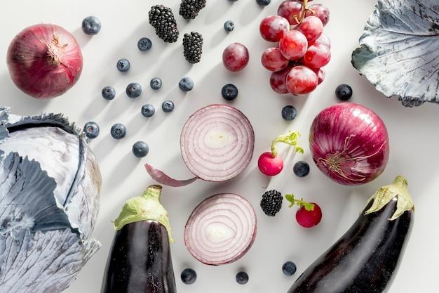 Bovenaanzicht van uien met druiven en aubergines