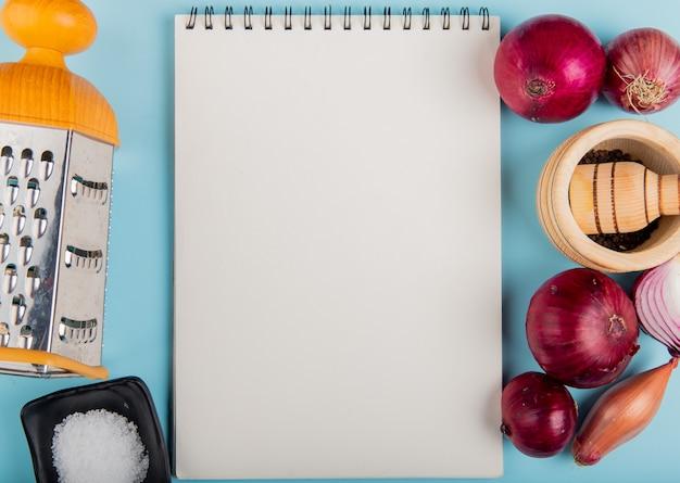 Bovenaanzicht van uien met zout, zwarte peper zaden en rasp rond notitieblok op blauwe oppervlak met kopie ruimte