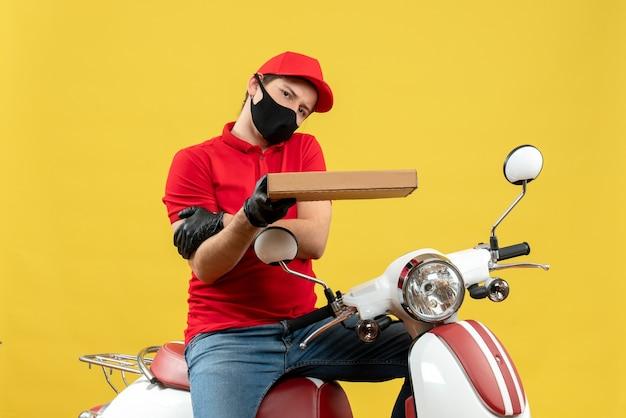 Bovenaanzicht van uitgeputte courier man met rode blouse en muts handschoenen in medische masker zittend op scooter holdingsvolgorde