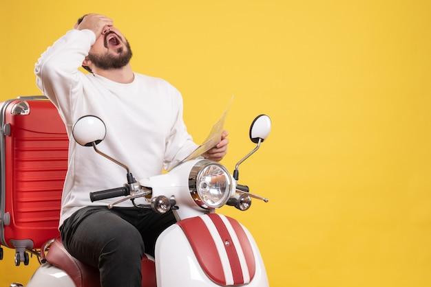 Bovenaanzicht van uitgeputte jonge kerel zittend op motorfiets met koffer erop met kaart op geïsoleerde gele achtergrond