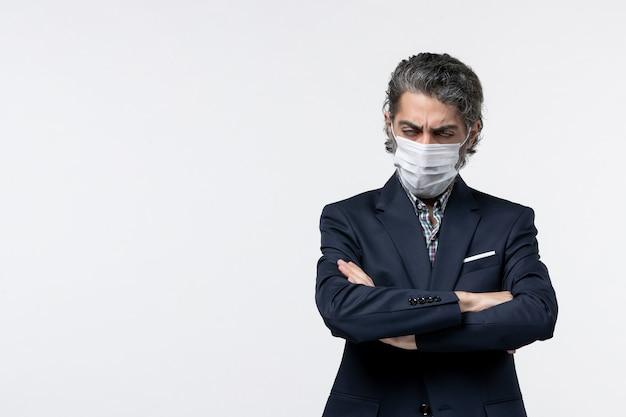 Bovenaanzicht van uitgeputte jonge zakenman in pak met masker en poseren voor camera op witte achtergrond