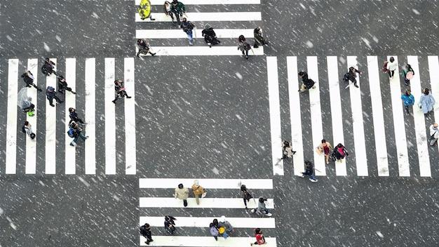 Bovenaanzicht van undefined japanse mensenmassa loopt aan kruisen