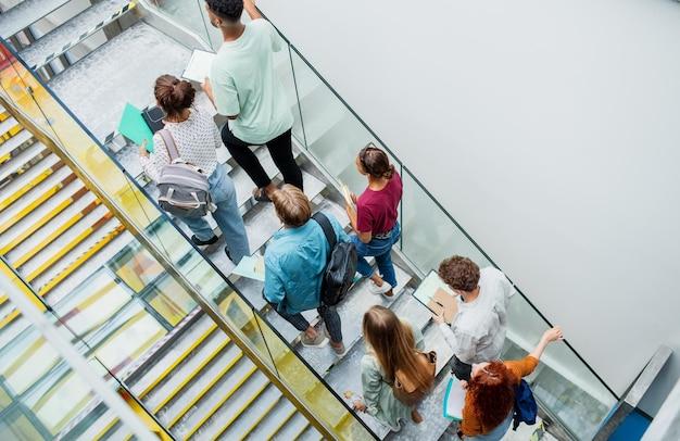 Bovenaanzicht van universiteitsstudenten die binnenshuis de trap oplopen, naar de camera kijken en zwaaien.