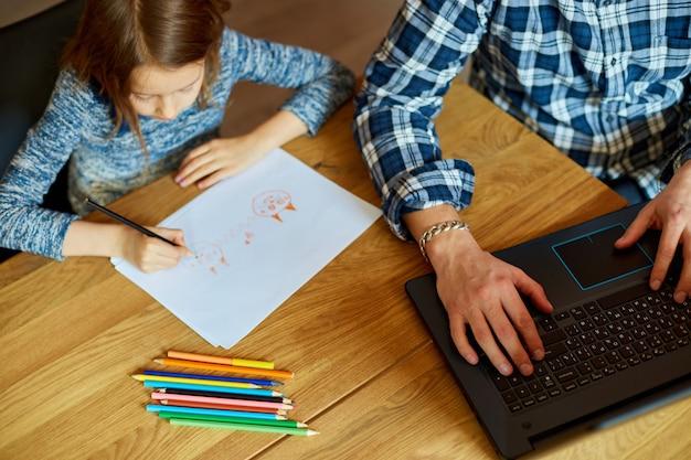 Bovenaanzicht van vader werkt in zijn kantoor aan huis op een laptop, haar dochter zit naast haar en tekenen