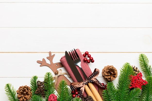 Bovenaanzicht van vakantie objecten op houten achtergrond. gebruiksvoorwerpen verbonden met lint op servet. kerstdecoraties en rendieren met kopie ruimte. nieuwjaar diner concept