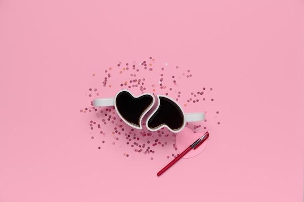 Bovenaanzicht van valentijnsdag concept met kopie ruimte. bekers met koffie, confetti, papier hart en pen op roze achtergrond.