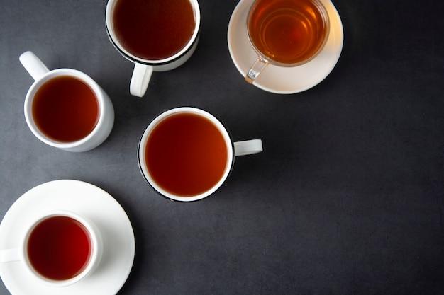 Bovenaanzicht van veel kopjes, mokken met hete thee drinken op donker