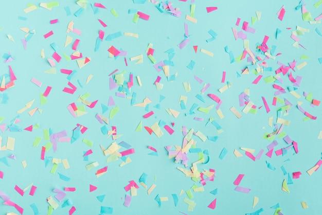 Bovenaanzicht van veelkleurige confetti op turkooizen achtergrond
