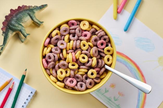Bovenaanzicht van veelkleurige cornflakes in een gele kom met kinderspullen op een lichtgele achtergrond