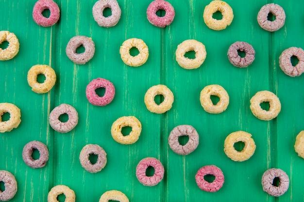 Bovenaanzicht van veelkleurige lus en gezonde granen geïsoleerd op groen oppervlak