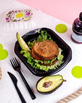 Bovenaanzicht van vegan sandwich met avocado en tomaten in een leveringsdoos
