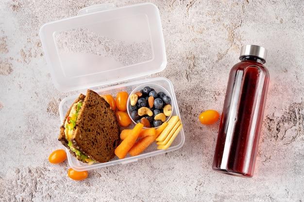 Bovenaanzicht van veganistische en gezonde schoollunch en fles met sap op grijze betonnen achtergrond