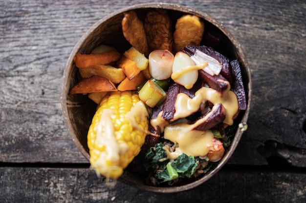 Bovenaanzicht van veganistische maaltijd met maïs, tempeh-eiwit en groenten geserveerd in een kom van kokosnoot buddha