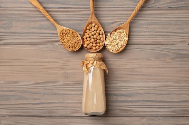 Bovenaanzicht van veganistische melk en granen in houten lepels op houten oppervlak kopie ruimte