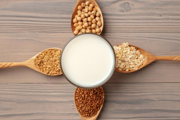 Bovenaanzicht van veganistische melk en granen in houten lepels op houten oppervlak