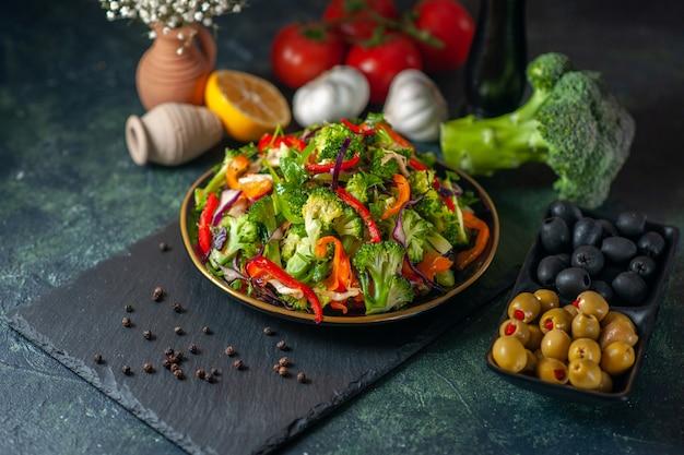 Bovenaanzicht van veganistische salade met verse ingrediënten in een bord op zwarte snijplank