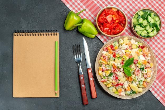 Bovenaanzicht van vegetarische salade met rood servet eronder en groentenbestek en blocnote aan de zijkant op donkergrijze achtergrond