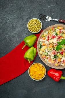 Bovenaanzicht van vegetarische salade op rood servet en met groenten en vork aan de zijkant op donkergrijze achtergrond